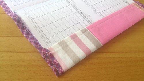 Hefteinband selbstgenäht: Rosa Einband aufgeklappt mit eingelegtem Hausaufgabenheft. Detailansicht