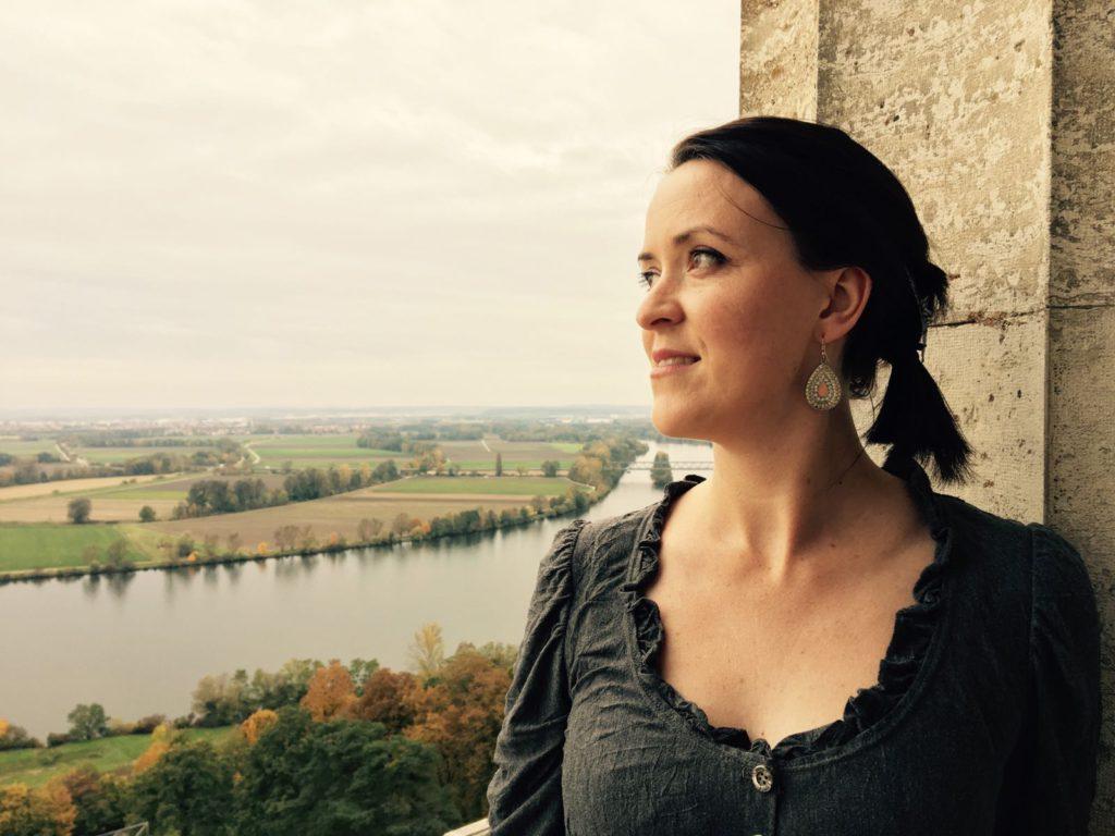 Kleid aus grauem crashed Jersey langärmelig, Portraitaufnahme, im Hintergrund sieht man die Donau und Regensburg