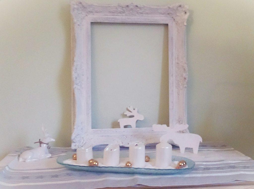 Adventsdekoration auf dem Schubladenschränkchen mit 4 Kerzen im Vordergrund, beide Elche aus Holz sitzen daneben, einem weißen Keramikhirsch und einem schönen romantisch verschnörkeltem weißen Bilderramen im Hintergrund