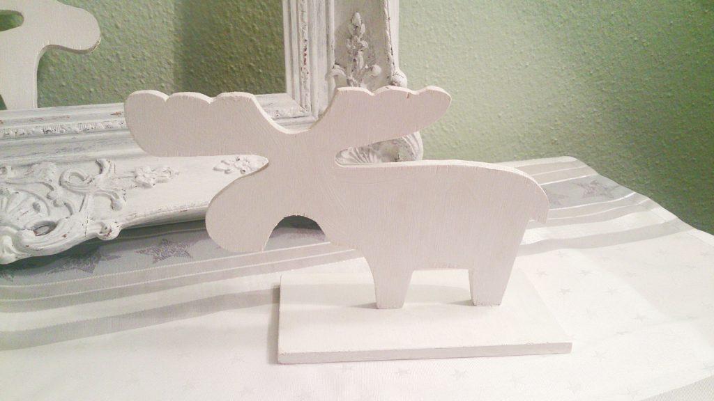 Beide weißen Elche aus Holz im Detail und dem schönen romantisch verschnörkeltem weißen Bilderramen im Hintergrund