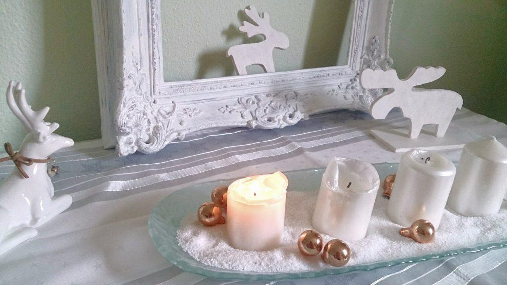 1. Advent, die erste Kerze brennt: Adventsdekoration auf dem Schubladenschränkchen mit 4 Kerzen im Vordergrund, beide Elche aus Holz sitzen daneben, einem weißen Keramikhirsch und einem schönen romantisch verschnörkeltem weißen Bilderramen im Hintergrund