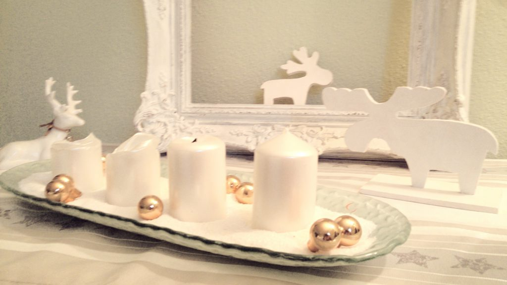 Detailbild von der Adventsdekoration auf dem Schubladenschränkchen mit 4 Kerzen im Vordergrund, beide Elche aus Holz sitzen daneben, einem weißen Keramikhirsch und einem schönen romantisch verschnörkeltem weißen Bilderramen im Hintergrund