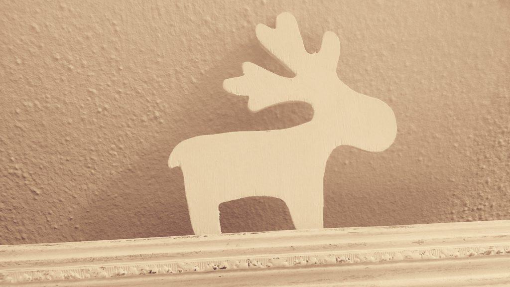 der kleine Holzelch im Detail, der an der Wand lehnt im verschnörkelten Bilderramen