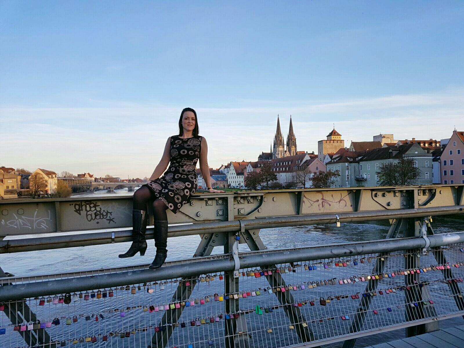 Im Jersey-Kleid und Shirt auf dem Brückengeländer über der Donau in orange Licht des Sonnenuntergangs getunkt. Im Hintergrund das Donauufer von Regensburg mit den beiden markanten Domspitzen von Regensburg