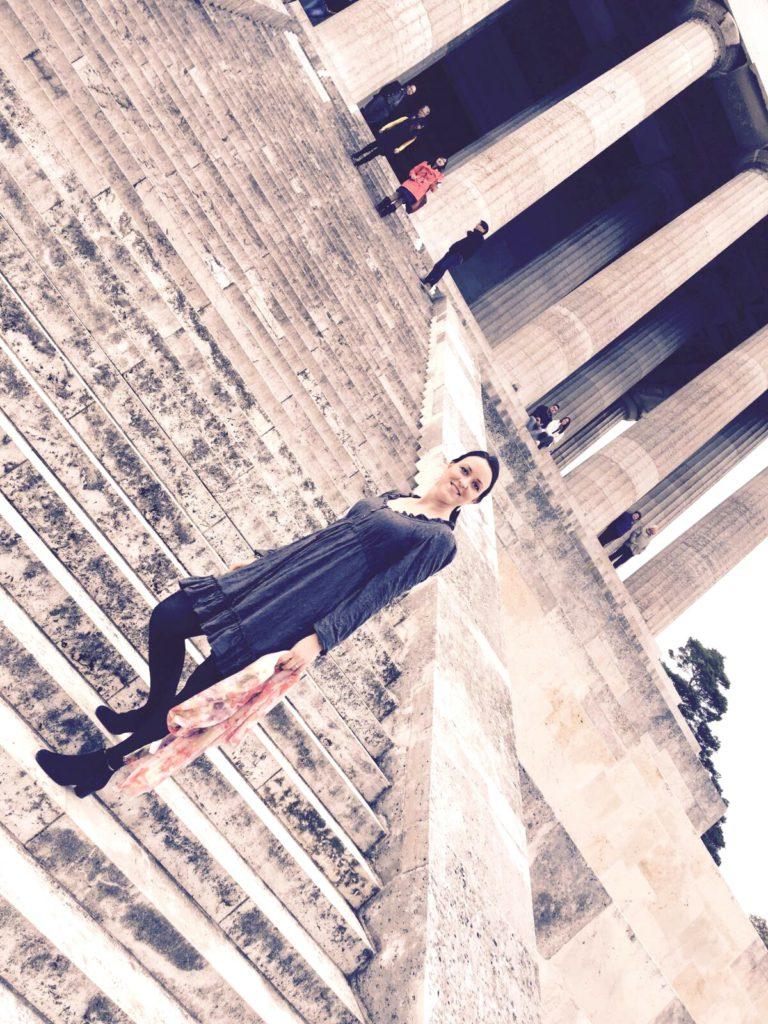 Kleid aus grauem crashed Jersey langärmelig, mit Schal, im Hintergrund sieht man die Stufen der Walhalla und einige Säulen