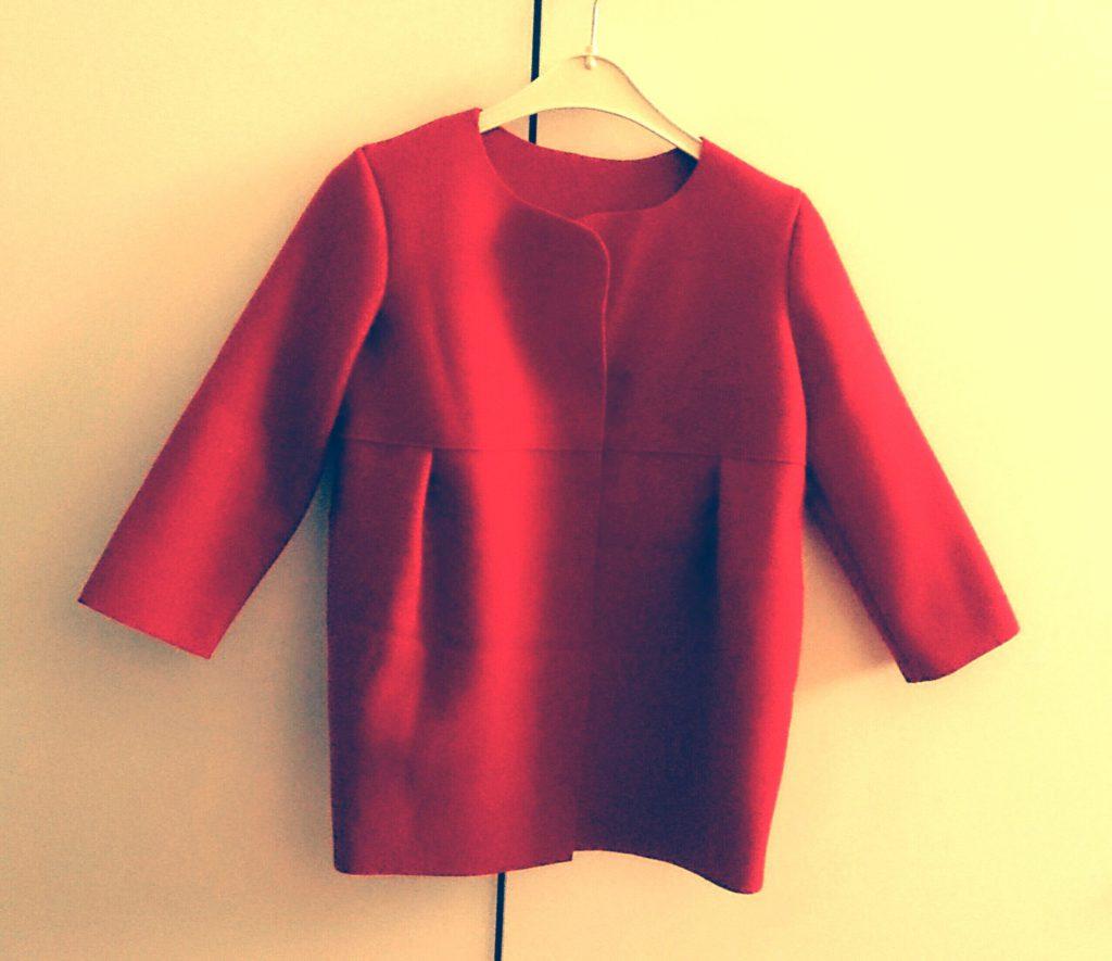roter Mantel hängt am Kleiderbügel