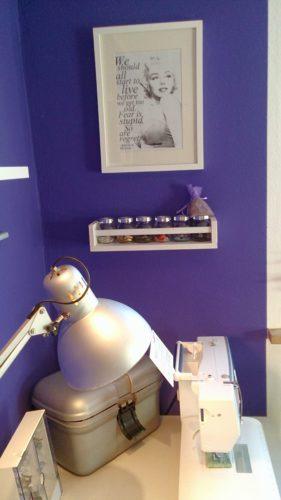 Ausschnitt Näheck nach dem Makeover: Schreibtisch mit Nähmaschine, Blick auf das Foto von Marylin Monroe mit ihrem Zitat eingerahmt in weiß an der lila Wand, darunter das Gewürzregal gefüllt mit Knöpfen