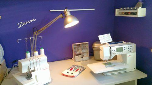Ausschnitt Näheck nach dem Makeover: Schreibtisch mit Nähmaschinen und silberne Lampe, Gewürzregal mit Knöpfen gefüllt