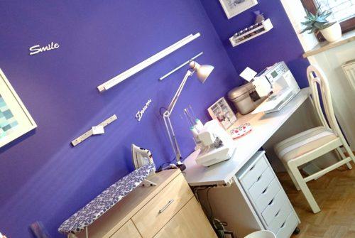"""Ausschnitt Näheck nach dem Makeover: weiße Holzschriftzüge """"Smile"""" und """"Dream"""" an der lila Wand,Stuhl, Schreibtisch mit Nähmaschinen und Rollconatiner vor der lila Wand"""