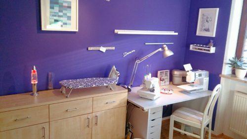 Gesamtsicht Näheck nach dem Makeover: Komode, Bügelbrett und Bügeleisen, Stuhl, Schreibtisch mit Nähmaschinen und Rollconatiner vor der lila Wand mit Bildern und Regalen
