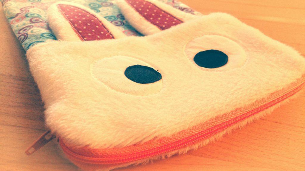 Hasentasche von vorne im Detail. Weißes Fellgesicht mit großen applizierten Augen, rosa Reißverschluss als Mund. Angenähte Ohren. Rücken und Bauch sind aus buntem Baumwollstoff