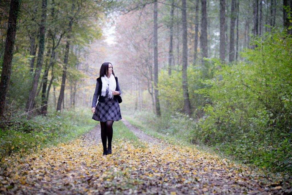 Spaziergang im Wald, nebliger Waldweg. Gesamtoutfit mit Rock, Shirt, Weste und Schal