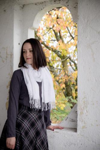 Rock, Shirt und Schal ohne Fellweste. Lehnt am Fensterbrett, draußen sieht man das Herbstlaub eines Baumes