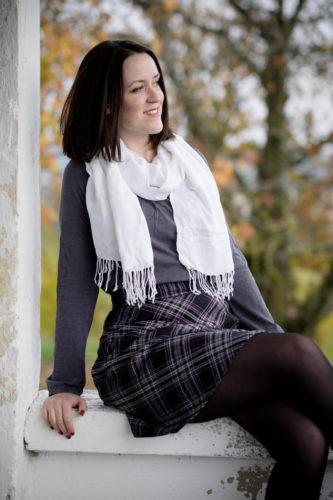 Rock, Shirt und Schal ohne Fellweste. Sitzend auf einer Fensterbank im Freien