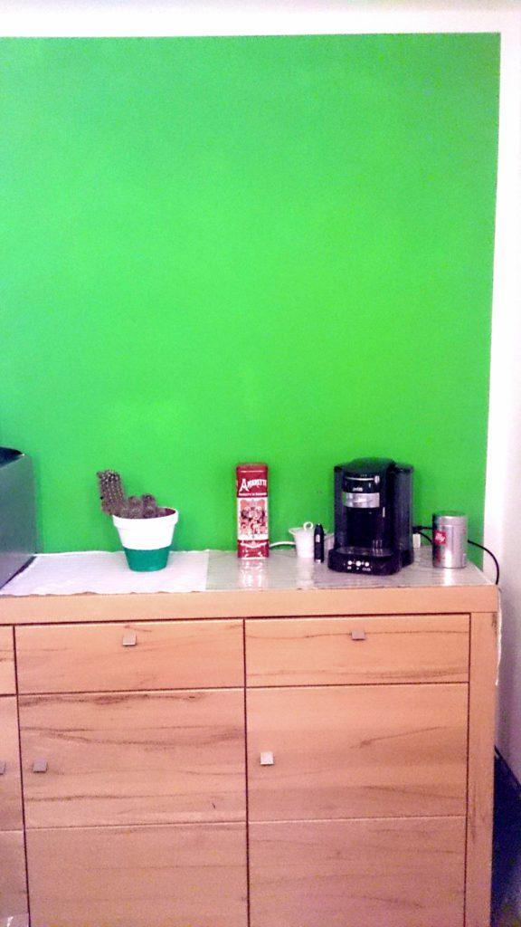 Blumentopf weiß und grün gestrichen vor der grünen Wand