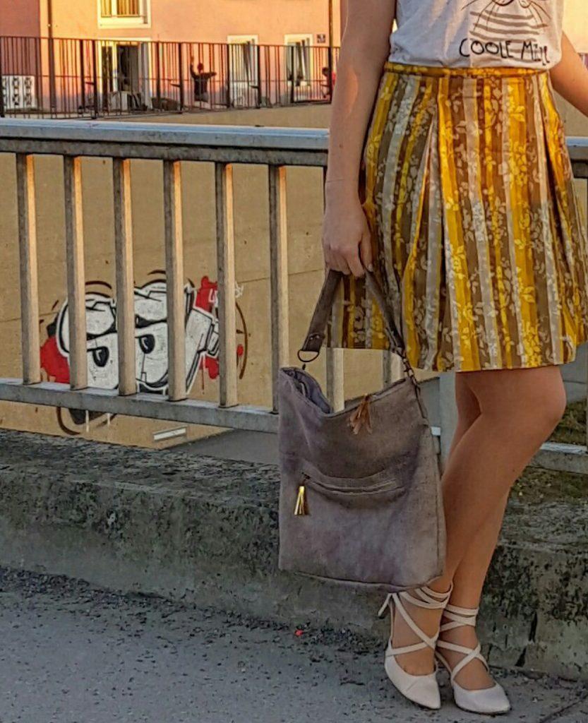 verschiedenArt: Chobe Bag aus Kunstleder und mit goldenen Lederquasten im Outfit mit dem Kellerfaltenrock