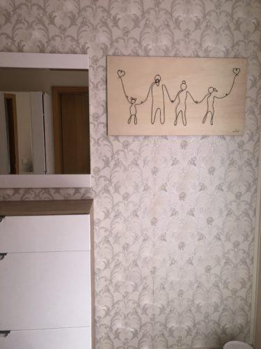 Das Bild hängt an der Wand, die mit einer romantisch verzierten silbernen Tapete beklebt ist. Neben dem Bild sieht man den Spiegel und ein sideboard