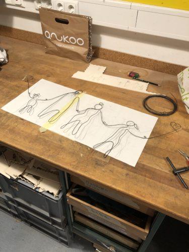 Der Draht ist fertig zum Familienportrait gebogen und liegt auf der gezeichneten Vorlage auf weißen Papier auf der Werkbank