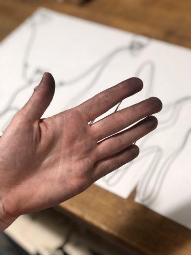 meine Hand mit schwarzen Rückständen vom schwarzen Stahldraht