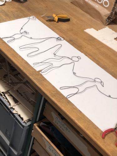 Der Draht ist fertig zum Familienportrait gebogen und liegt auf einem weißen Papier auf der Werkbank