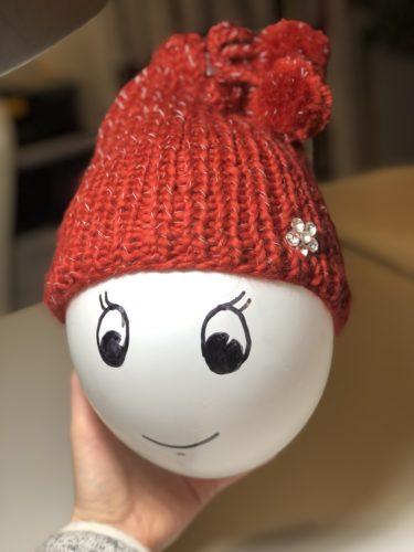 Die Loopmütze sitzt als Mütze auf einem weißen Luftballon anstelle eines Kinderkopfes. Dem Luftballon wurde ein freundliches Gesicht aufgemalt.