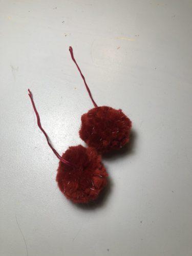 zwei rote Bommel aus der roten Glühwürmchenwolle