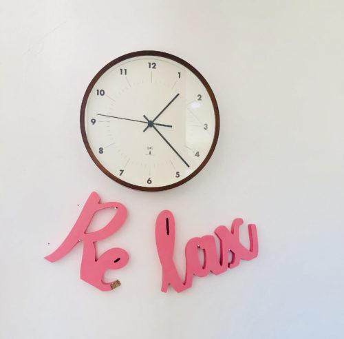 "Uhr an der Wand. Darunter ein zerbrochener Schriftzug aus Holz ""Relax"""