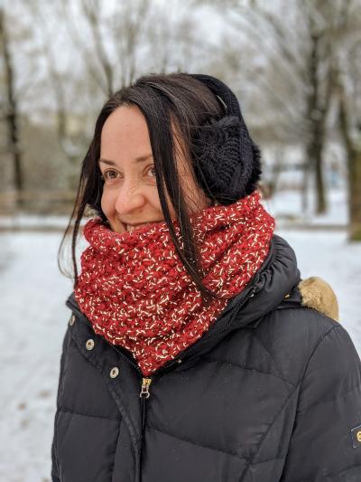 verschiedenArt lachend vor winterlicher Parklandschaft mit schwarzem Mantel und weinrotem Loop Schal um den Hals. Der Schal reflektiert das Licht des Blitzes.