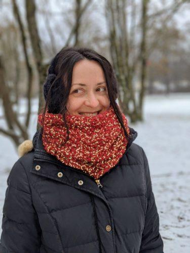 verschiedenArt vor winterlicher Parklandschaft mit schwarzem Mantel und weinrotem Loop Schal um den Hals. Der Schal reflektiert das Licht des Blitzes.
