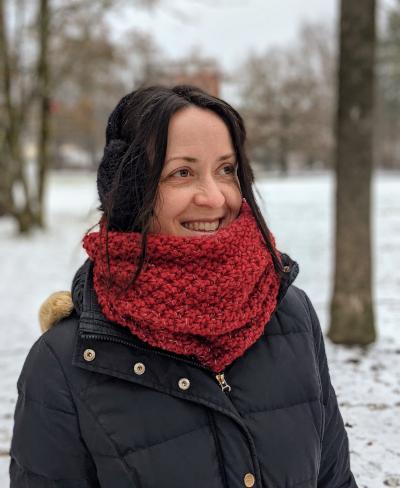 verschiedenArt vor winterlicher Parklandschaft mit schwarzem Mantel und weinrotem Loop Schal um den Hals. Der Schal reflektiert ist weinrot und man sieht das Perlmuster gut.