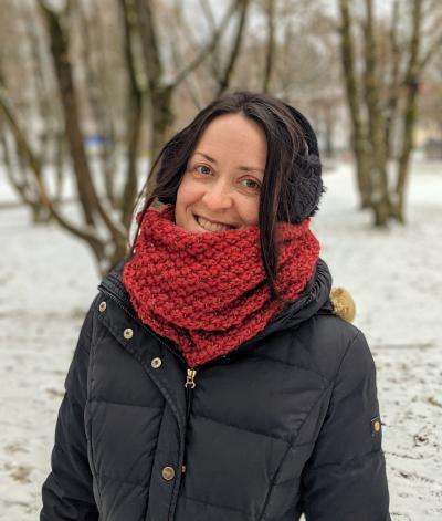 verschiedenArt frontal vor winterlicher Parklandschaft mit schwarzem Mantel und weinrotem Loop Schal um den Hals. Der Schal ist weinrot und man sieht das Perlmuster gut.