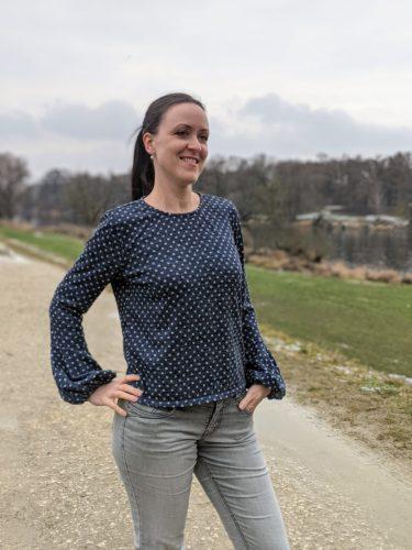 Blauer Pullover mit Puffärmeln an den Ärmelbündchen. Der Pullover hat gleichmäßige silbergraue Punkte.