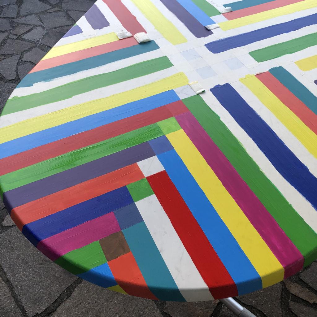 Der Tisch ist schon mit vielen bunten Streifen bemalt. An den Stellen wo sich zwei Streifen treffen, mischen sich die beiden Farben der Streifen.