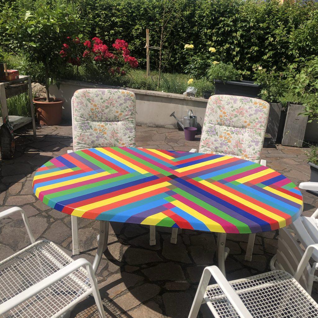 bunt bemalter Gartentisch auf der Terrasse mit Gartenstühlen