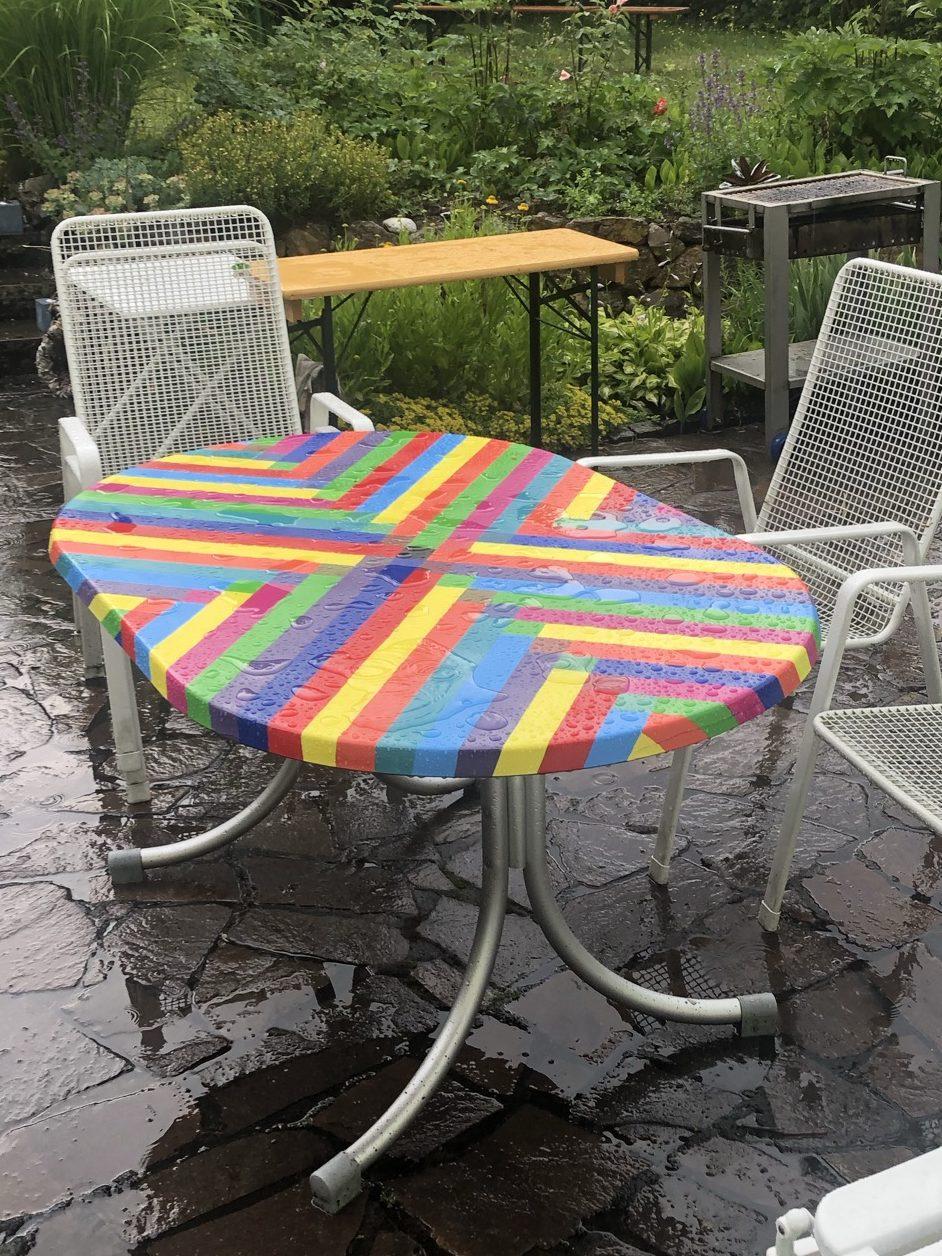 bemalter Gartentisch steht im strömenden Regen auf der Terrasse. Das Wasser perlt gut ab, kleine Pfützen bilden sich auf der Oberfläche.