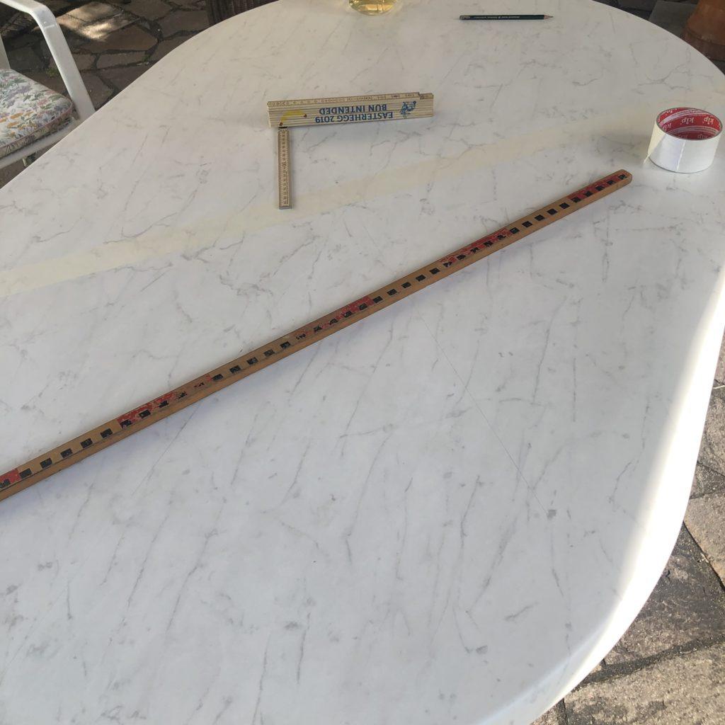 Der noch weiße Kunststofftisch mit einem ersten Streifen Kreppband beklebt.